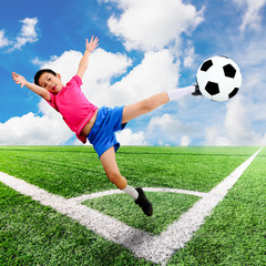 Asian boy with soccer ball at soccer field and blue sky