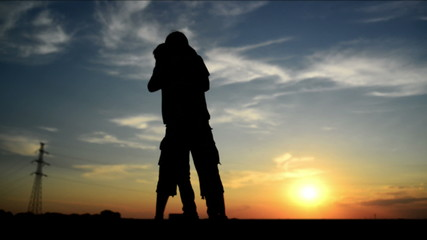 Lovers on a date in sunset, hugging and kissing. Romantic scene.