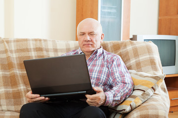gray-haired man working at his laptop
