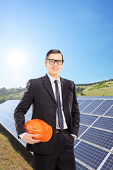 Male engineer standing in a field with solar panels