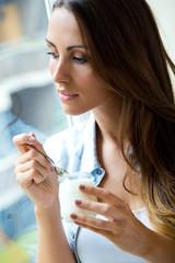 Young woman at home eating yogurt