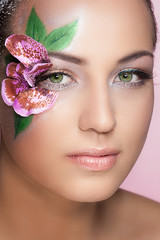 Portrait of beautiful girl with flower on her face
