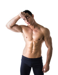 Shirtless muscular male bodybuilder wiping sweat off