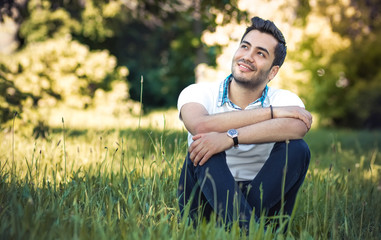 Happy young man sitting on meadow