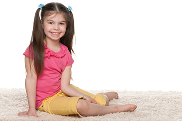Happy little girl sits on the white carpet