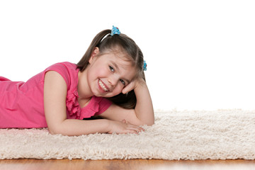 Laughing little girl on the white carpet