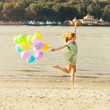 Woman jumping on the beach with balloons