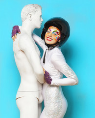 Model with bright creative make up with helmet and male dummy