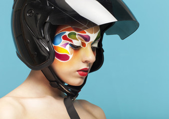 Model with bright creative make up with helmet