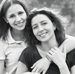 Young smiling woman with her teen daughter outdoors