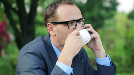 Businessman talking on cellphone and drinking coffee in garden