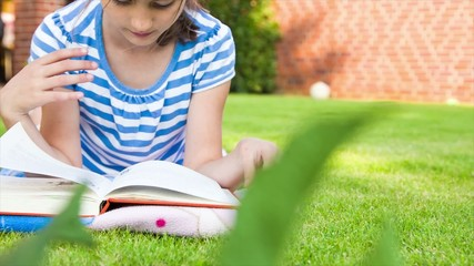 Little girl reading a book in summer on grass.dolly shot