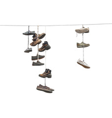 Old worn boots or shoes hang on a cable