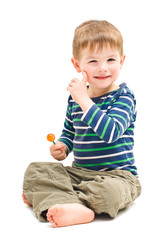 Portrait cute cheerful boy sitting with lollipop