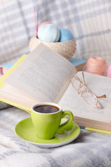 Cup of coffee and yarn for knitting on plaid with books