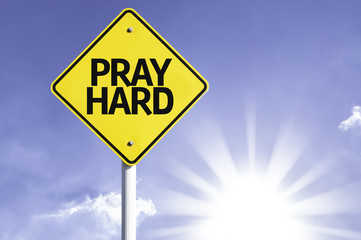 Pray Hard road sign with sun background