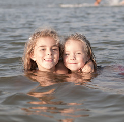 Two Little girls swimming at the beach and looking at camera.