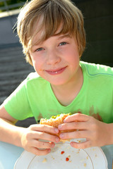 smiling boy is eating hamburger
