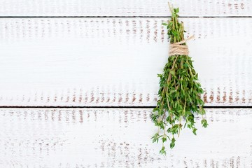 bunch of thyme on a white wooden background
