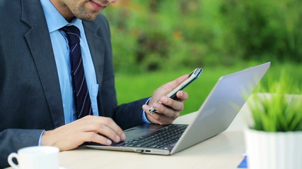 Businessman working with smartphone and laptop in the garden