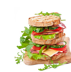 Sandwich with ham, cheese and fresh vegetables on white backgrou