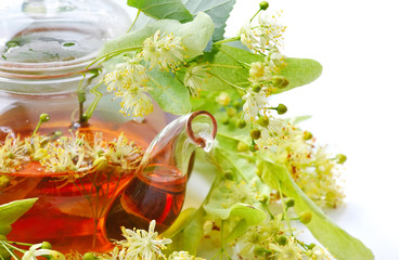 Teapot with linden tea and flowers, close-up
