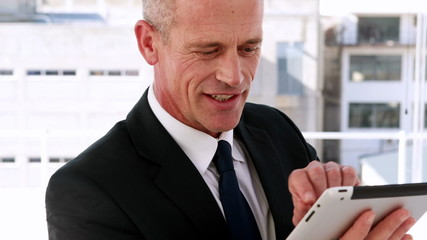 Businessman using tablet pc and smiling at camera