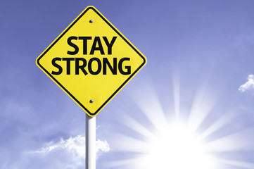 Stay Strong road sign with sun background