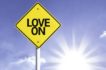 Love On road sign with sun background