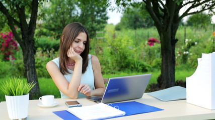 Bored young businesswoman sitting by the table in garden