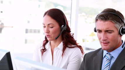 Call centre agents working and talking on headsets