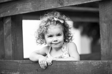 monochrome portrait of little girl in farn yard
