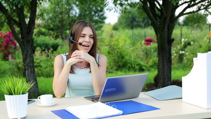 Female helpdesk operator with laptop talking to customer