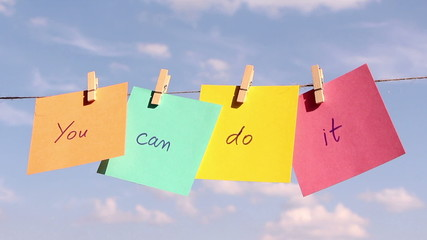 "sentence ""You Can Do It"" on colorful paper pinched on a rope."