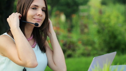 Happy female helpdesk operator with laptop in the garden