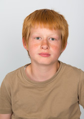 boy with red hair looking serious