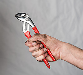 hand with a pipe wrench