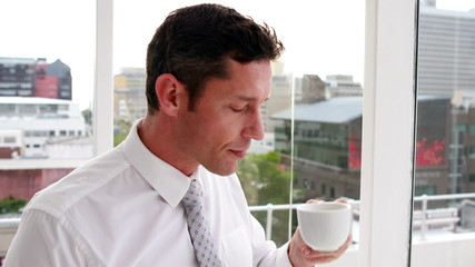 Handsome businessman drinking coffee and looking out window
