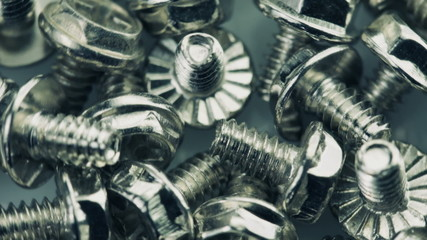 Close-up of steel bolts turning in a seamless loop.