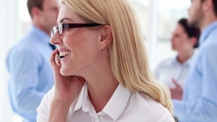Businesswoman talking on phone with colleagues behind her
