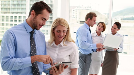 Business team using tablet and smiling at camera together
