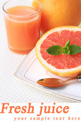 Half of grapefruit, glass of fresh juice and spoon