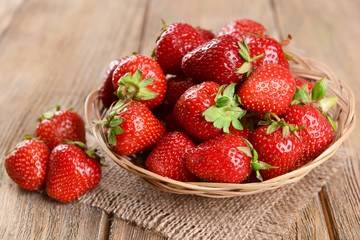 Ripe sweet strawberries in wicker basket on table close-up