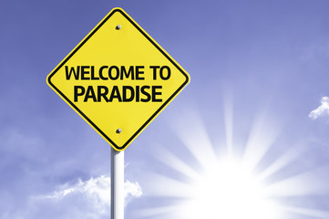 Welcome to Paradise road sign with sun background