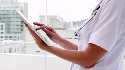 Nurse in tunic using tablet pc