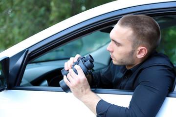 Man in car with binoculars