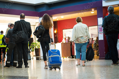 Travellers, passengers at an airport, train station. - 67635882