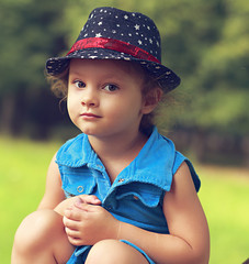 Fashion beautiful child girl in blue jeans dress sitting
