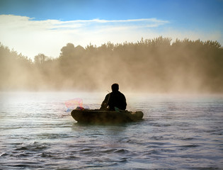 The silhouette of a fisherman in the fog on the river