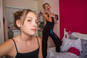 Two young girls talking on the phone in their room